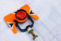 Orange theodolite prism lies on a background geodetic maps of the area Kuvituskuvat
