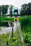 Blue surveying equipment total station on a background of lake and forest Stock Photos