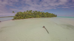 Tetiaroa, French Polynesia - Flying over a woman sitting in a blue lagoon - stock footage