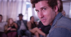 Portrait of Handsome young hipster man smiling at camera with group of friends Stock Footage