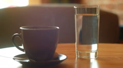 Cup of coffee and glass of water on he table Stock Footage
