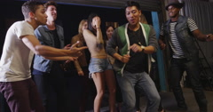 Happy fun loving hipster mixed race group of friends dancing late into night in Stock Footage