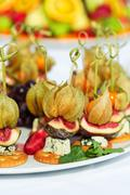 Canapes with physalis, fig, cheese and crackers - stock photo