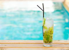 Mohito mojito drink with ice mint and lime near swimming pool - stock photo