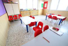 Nursery classroom with school desks and small red chairs Stock Photos