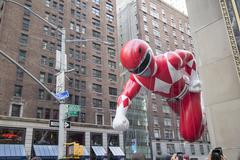 Red Power Ranger flying between New York City buildings 2015 - stock photo