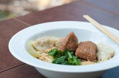 Egg noodle with delicious stewed pork and dumpling, closed up. Stock Photos