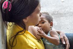 Stock Photo of Woman breast feeding a child begging