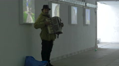 Man playing an according in an underground passage in Bucharest Stock Footage