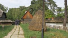 Tourists walking on an alley between houses at the Village Museum in Bucharest Stock Footage