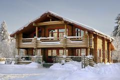 Log house covered in snow during winter. - stock photo