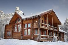 Log home winter with large windows, balcony and porch, daytime. Stock Photos
