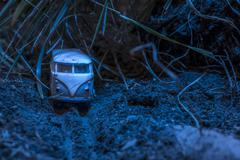 Vintage bus VW. Small metal toy in the nature in the night - stock photo
