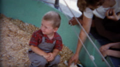 1954: Mom teaching kids at petting zoo about rabbits and sheep. Stock Footage