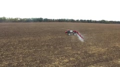 Red tractor plowing the field corn. aerial shot Stock Footage