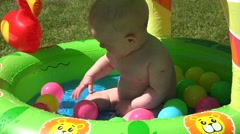 Little baby girl play in water  inflatable pool with small ball. 4K Stock Footage