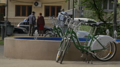 Green bikes parked near a fountain in Bucharest Stock Footage
