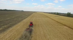 Farmer in red tractor preparing land for sowing. aerial shot Stock Footage