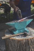 Blacksmith forges iron on anvil Stock Photos