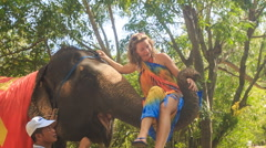 Tourist takes seat onto elephant's trunk to ride in tropical park Stock Footage