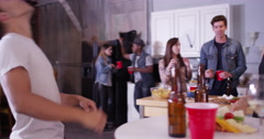 Group of young fun loving 20 somethings partying in kitchen and toasting to Stock Footage
