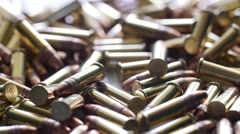 Stock Video Footage of Slow motion a dolly shot of a pile of .22 ammunition bullets