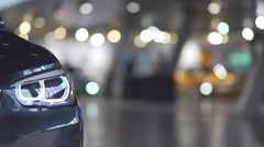 headlamp of a new car in the showroom with the background movement of people - stock footage