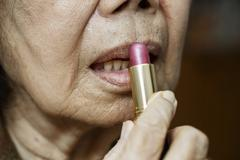 Elderly asian woman applied lipstick - stock photo