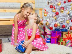 Girl kissing her sister because she gave her a gift - stock photo
