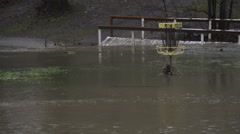Herbert Hoover footbridge and disc golf basket in flooded park Stock Footage