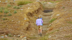Tired male and female tourists climbing upstairs, sightseeing tour on vacation Stock Footage