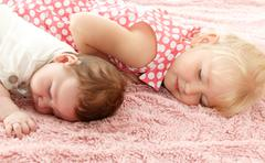 Children lie on the mat - stock photo