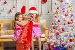 Two girls having fun trying to untie the bag with gifts - stock photo