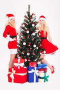 Beautiful happy sisters twins near Christmas tree and gifts - stock photo