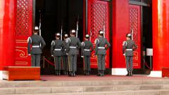 Honour guards salute after commander order, stand against Shrine entrance Stock Footage