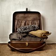 Old suitcase with some warm clothing Stock Photos