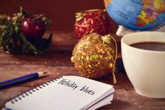 Christmas ornaments, cup of coffee, globe and text holidays blues Stock Photos