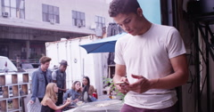 Young attractive hipster man texting on phone while at a cool party Stock Footage