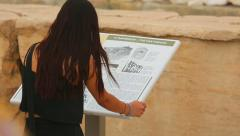 Young female reading information about Parthenon temple on tourist guide table Stock Footage