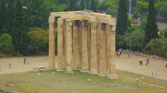 Remains of ancient temple, tourists with umbrellas view landmark, rainy weather Stock Footage