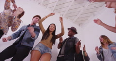 Low angle view of mixed race group of young hipster friends dancing in white Stock Footage