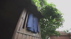 Blue jacket hanging on the wood background Stock Footage