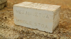 English and ancient Greek inscription Middle Stoa on stone table for tourists Stock Footage