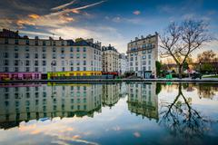 Stock Photo of Buildings reflecting in Canal Saint-Martin at sunset, in Paris, France.