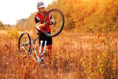 Bike repair. Young man repairing mountain bike - stock photo