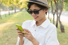 portrait of young beautiful asian woman and smart phone in hand smiling tooth - stock photo