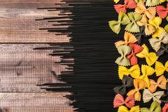 Black raw long spaghetti with colorful farfalle - stock photo