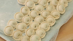 A baking tray with dumplings is standing on the table - stock footage
