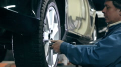 Mechanic unscrews the bolts out of the wheel Stock Footage