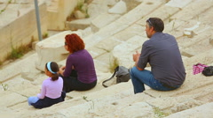 Parents and daughter sitting on ancient amphitheater seats, family travel Stock Footage